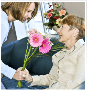 Caregiver giving flowers to a senior