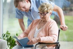 Elder in wheelchair reading book